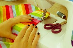 Le processus de couture, la machine à coudre cousent des mains du ` s de femmes machine à coudre et ciseaux femelles Photo stock