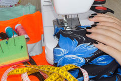 Le processus de couture, la machine à coudre cousent des mains du ` s de femmes machine à coudre et ciseaux femelles Images libres de droits
