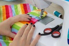 Le processus de couture, la machine à coudre cousent la machine à coudre de mains du ` s de femmes machine à coudre et ciseaux fe Photographie stock libre de droits