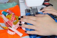 Le processus de couture, la machine à coudre cousent la machine à coudre de mains du ` s de femmes machine à coudre et ciseaux fe Photos libres de droits