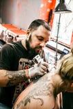 Le processus de créer un tatouage au dos d'une fille Photographie stock libre de droits