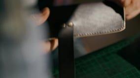Le processus de la fabrication un portefeuille en cuir fait main L'artisan combine des éléments avec des rivets Cuir fait main banque de vidéos