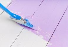Le processus de peindre le bois embarque avec la brosse et la couleur violette Image stock