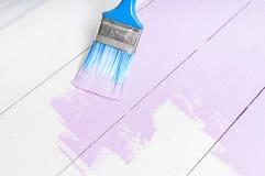 Le processus de peindre le bois embarque avec la brosse et la couleur violette Photo libre de droits