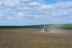 Le processus de répandre un engrais granulé par minerai avec un agrégat fixé à un tracteur photos stock