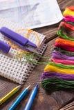 Le processus du point de croix Aiguilles, soie, plan, ciseaux, crayons et stylo sur une table en bois Images libres de droits