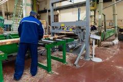 Le processus du travailleur avec la circulaire a vu la machine à la croix c de faisceau en bois image libre de droits