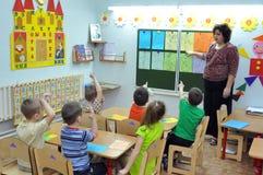 Le professeur a affaire avec les enfants dans le jardin d'enfants Photos libres de droits