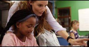 Le professeur aidant l'école badine sur le PC dans la salle de classe