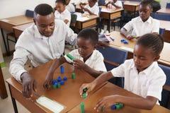 Le professeur aidant l'école primaire badine le compte avec des blocs image libre de droits