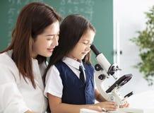 Le professeur aide l'enfant à entreprendre l'expérience avec le microscope images libres de droits