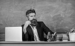 Le professeur a concentré le maître mûr barbu écoutant avec l'attention Le tenue de soirée de professeur reposent la salle de cla photos stock