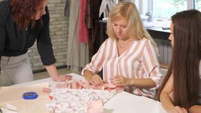 Le professeur d'ouvrière couturière parle des étudiants au sujet des manières de traiter le tissu dans l'atelier banque de vidéos