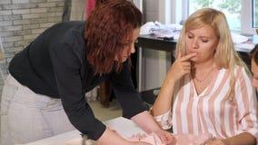 Le professeur d'ouvrière couturière parle des étudiants au sujet des manières de traiter le tissu dans l'atelier clips vidéos