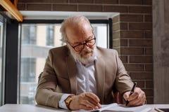 Le professeur d'une chevelure gris comcentrated sur son travail dans la salle de grenier Image libre de droits