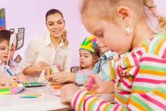 Le professeur dans des enfants d'aide de jardin d'enfants font le métier de papier Images libres de droits