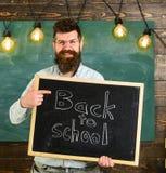 Le professeur dans des lunettes tient le tableau noir avec l'inscription de nouveau à l'école Homme avec la barbe et moustache su Photos libres de droits