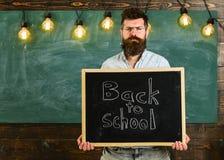 Le professeur dans des lunettes tient le tableau noir avec l'inscription de nouveau à l'école Homme avec la barbe et moustache su Photos stock