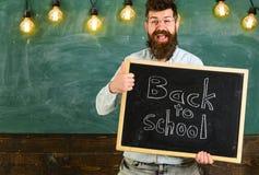 Le professeur dans des lunettes tient le tableau noir avec l'inscription de nouveau à l'école L'homme avec la barbe sur le visage Image libre de droits