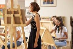 Le professeur de dessin de charme dans la belle robe montre la technique de dessin au chevalet dans le studio d'art photo stock