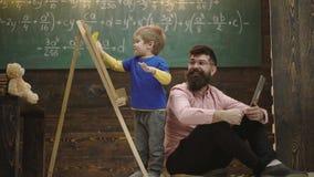 Le professeur de sourire en verres regarde l'enfant essuyant le tableau Père et enfant blond excité apprenant des maths Garçon de banque de vidéos