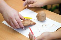 Le professeur enseigne l'étudiant à sculpter avec de l'argile Photos libres de droits