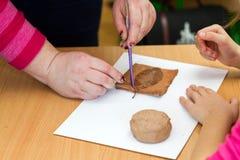Le professeur enseigne l'étudiant à sculpter avec de l'argile Image libre de droits