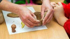 Le professeur enseigne l'étudiant à sculpter avec de l'argile Image stock