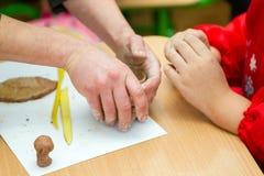 Le professeur enseigne l'étudiant à sculpter avec de l'argile Photo stock