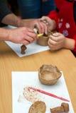 Le professeur enseigne l'étudiant à sculpter avec de l'argile Photographie stock