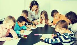 Le professeur et l'âge élémentaire badine le dessin à la salle de classe Photographie stock