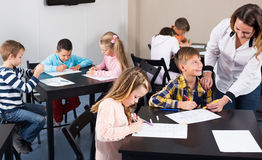 Le professeur et l'âge élémentaire badine le dessin à la salle de classe Images libres de droits