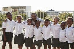 Le professeur et l'école primaire badine dans le terrain de jeu, portrait Photographie stock libre de droits