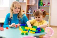 Le professeur et l'élève du cours préparatoire jouent avec des briques de construction Photos libres de droits