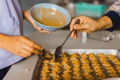Le professeur et l'étudiant font des biscuits de Singapour à partir de la pâte à l'école Images stock