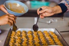 Le professeur et l'étudiant font des biscuits de Singapour à partir de la pâte à l'école Images libres de droits