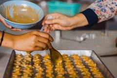 Le professeur et l'étudiant font des biscuits de Singapour à partir de la pâte à l'école Photo libre de droits