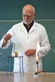 Le professeur mélange des produits chimiques dans un laboratoire images stock