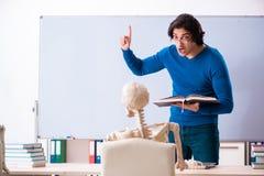 Le professeur masculin et l'?tudiant squelettique dans la salle de classe photo stock