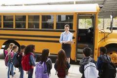Le professeur prenant un s'inscrire d'école badine en l'autobus scolaire photos libres de droits