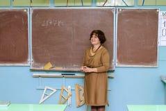 Le professeur se tient au tableau noir dans la salle de classe et décide Images stock