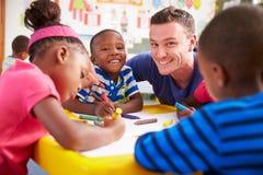 Le professeur volontaire aidant une classe d'école maternelle badine le dessin Images stock
