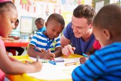 Le professeur volontaire aidant une classe d'école maternelle badine le dessin Photo stock