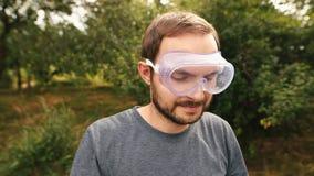 Le professionallawngräsklippningsmaskinen som bär genomskinligt exponeringsglasskydd och och isolering av hörlurar stock video