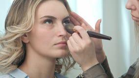 Le professionnel composent l'artiste appliquant la poudre à un jeune visage modèle Photographie stock libre de droits