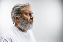Le profil de l'homme d'affaires sérieux regardant loin sur le fond blanc Photographie stock