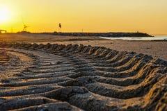 Le profil du mobile de nettoyage de plage est illuminé par le lever de soleil Photos stock