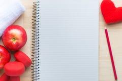 Le programme de formation de forme physique avec des haltères, mélange porte des fruits, serviette, carnet vide Vue de ci-dessus  photographie stock