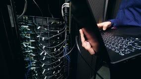 Le programmeur masculin fonctionne avec un ordinateur portable, vérifiant l'ordinateur de centre de traitement des données Concep banque de vidéos