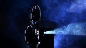 Le projecteur de film tourne le film dans le studio foncé fumeux Rayons de projection banque de vidéos